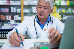 Pharmacist writing prescriptions for medicines. In pharmacy Royalty Free Stock Images