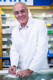 Pharmacist writing prescriptions for medicines. Portrait of pharmacist writing prescriptions for medicines in pharmacy Stock Image