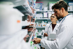 Pharmacists checking inventory at hospital pharmacy. Two pharmacist working in drugstore. Male and female pharmacists checking medicines inventory at hospital