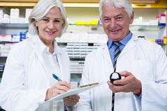 Pharmacists checking and writing prescription for medicine Stock Image