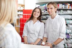 Pharmacists with Customer in Store Royalty Free Stock Images