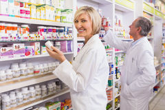 Pharmacists in lab coat looking at medicine Stock Photography