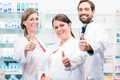 Pharmacists in pharmacy showing thumbs up royalty free stock image