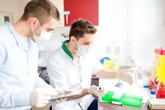 Pharmacists and scientist carrying out experiments in laboratory Stock Photos