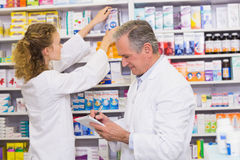 Pharmacists searching medicines with prescription Royalty Free Stock Photo