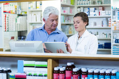 Pharmacists using digital tablet at counter Royalty Free Stock Photography