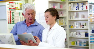 Pharmacists using digital tablet at counter. In pharmacy stock video