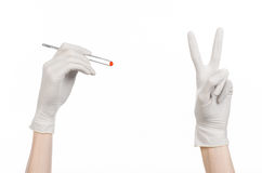 Pharmacology and Medical theme: doctor's hand in a white glove holding tweezers with red pill capsule isolated on white background. Studio Royalty Free Stock Photo