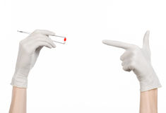 Pharmacology and Medical theme: doctor's hand in a white glove holding tweezers with red pill capsule isolated on white background Royalty Free Stock Images