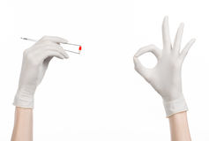 Pharmacology and Medical theme: doctor's hand in a white glove holding tweezers with red pill capsule isolated on white background. Studio Stock Images