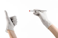 Pharmacology and Medical theme: doctor's hand in a white glove holding tweezers with red pill capsule isolated on white background Stock Photography