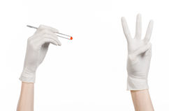 Pharmacology and Medical theme: doctor's hand in a white glove holding tweezers with red pill capsule isolated on white background Royalty Free Stock Photos