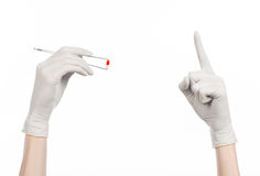 Pharmacology and Medical theme: doctor's hand in a white glove holding tweezers with red pill capsule isolated on white background. Studio Stock Photography
