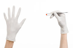 Pharmacology and Medical theme: doctor's hand in a white glove holding tweezers with red pill capsule isolated on white background. Studio Stock Photos