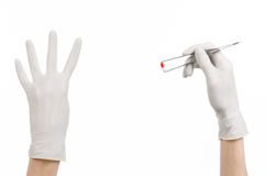 Pharmacology and Medical theme: doctor's hand in a white glove holding tweezers with red pill capsule isolated on white background. Studio Royalty Free Stock Photography