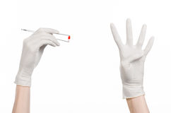Pharmacology and Medical theme: doctor's hand in a white glove holding tweezers with red pill capsule isolated on white background. Studio Royalty Free Stock Image