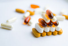 Pharmacology. The pyramid of capsules sports nutrition on white background Stock Images