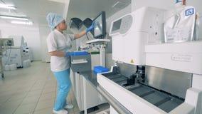 Pharmacutical试验室工怍人员在机器的显示器键入,执行血样测试  股票录像