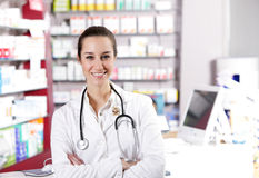 At pharmacy. A smiling young woman pharmacist with stethoscope Stock Photos