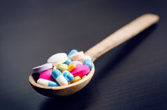 Pharmacy background on a black table with measuring tape. Tablets on a wooden spoon. Pills. Medicine and healthy. Close up of caps. Ules Royalty Free Stock Photos