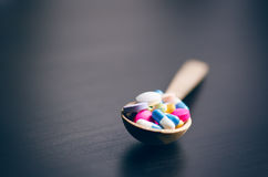 Pharmacy background on a black table with measuring tape. Tablets on a wooden spoon. Pills. Medicine and healthy. Close up of caps royalty free stock photos