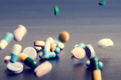 Pharmacy background on a dark table. Levitation pills. Tablets on a dark background which falling down. Pills.Medicine and health Stock Images