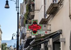A Pharmacy and baroque street lamps in Sorrento, Italy. Pictured is a sign for a pharmacy and baroque street lamps in Sorrento. Sorrento is a coastal town in Stock Images