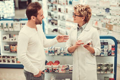 At the pharmacy. Beautiful pharmacist is suggesting drug to a client at the pharmacy and smiling Royalty Free Stock Photography
