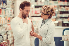 At the pharmacy. Beautiful pharmacist is talking to a client at the pharmacy, men is having a sore throat Stock Images