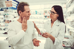 At the pharmacy. Beautiful young female pharmacist is talking to a client at the pharmacy, men is having a toothache royalty free stock image
