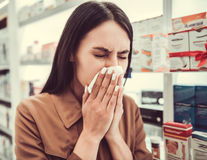 At the pharmacy. Beautiful young woman is wiping nose while searching for a medication at the pharmacy Stock Images