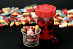 Pharmacy. Capsules with medication and drug solution in containers isolated on a black background Stock Images
