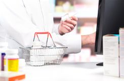 Pharmacy cashier or clerk at counter. Pharmacist using cash register. Druggist with pill bottles in shopping basket in drug store. Sales person touching Royalty Free Stock Image