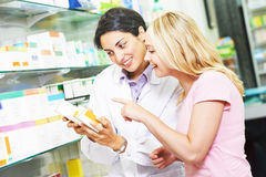 Pharmacy chemist consulting woman in drugstore Royalty Free Stock Photography
