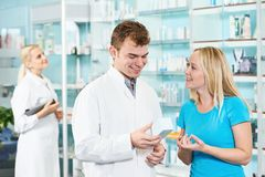 Pharmacy chemist and woman in drugstore Royalty Free Stock Images