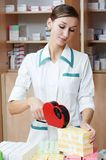 Pharmacy chemist woman labeling drugs. Pharmacist chemist woman marking drugs in pharmacy drugstore warehouse Royalty Free Stock Images