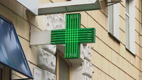 Pharmacy, drug store green neon cross lighted at daytime, city. Stock footage stock footage