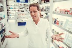 At the pharmacy. Handsome client is looking at camera and lifting hands in dismay stock photo