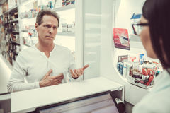 At the pharmacy. Handsome client is talking to a beautiful female pharmacist at the cash desk Royalty Free Stock Photo