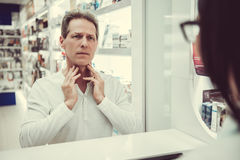 At the pharmacy. Handsome client is talking to a beautiful female pharmacist at the cash desk and showing that he has a sore throat Royalty Free Stock Photo