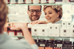 At the pharmacy. Handsome pharmacist is suggesting a medicine to a beautiful female client at the pharmacy and smiling stock photos