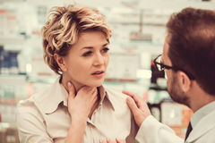 At the pharmacy. Handsome pharmacist is suggesting a medicine to a beautiful female client at the pharmacy. Woman is having a sore throat Stock Photo