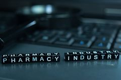 Pharmacy Industry text wooden blocks in laptop background. Business and technology concept stock image