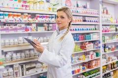 Pharmacy intern writing on clipboard Royalty Free Stock Photo