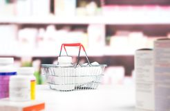 Pharmacy with medication and shelves. Shopping basket full of medicine and pill bottles on the counter in drugstore. Medical retail business and pharmaceutical Stock Images