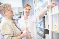Pharmacy. Pharmacist with client examining medicinal products Royalty Free Stock Photography