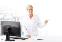 Pharmacy. Portrait of middle age pharmacist woman standing at pharmacy. Smiling woman wearing lab coat and working on computer while she shows something with her Royalty Free Stock Photography