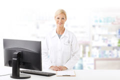 Pharmacy. Portrait of middle age pharmacist woman standing at pharmacy. Smiling woman wearing lab coat while working on computer and looking at camera Royalty Free Stock Image