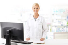Pharmacy. Portrait of middle age pharmacist woman standing at pharmacy. Smiling woman wearing lab coat while working on computer and looking at camera Stock Image