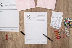 Pharmacy receipt with egc, pills and syringe. On desk Stock Photos